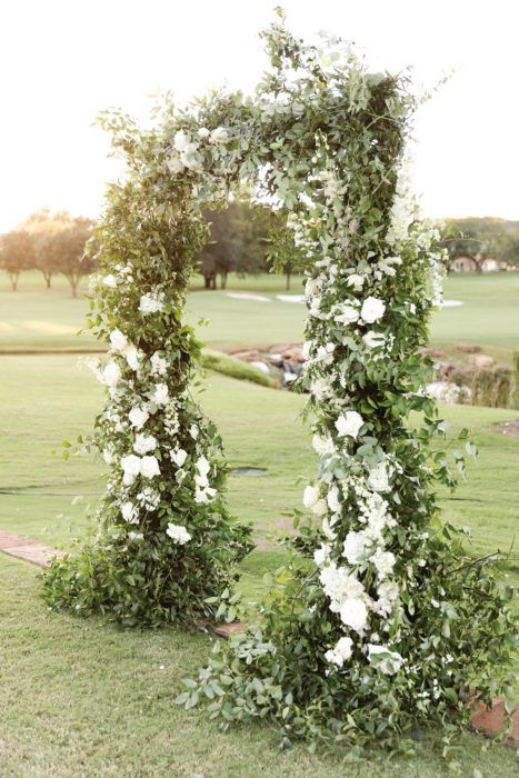 a chic garden wedding arch decorated with greenery and white blooms is a very chic and stylish idea that will never go out of style