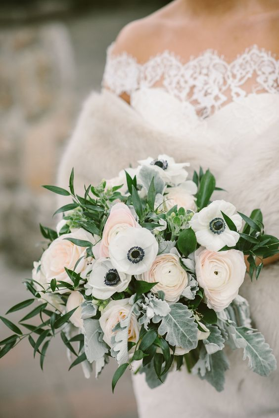 a chic spring wedding bouquet of white anemones, pink ranunculus, greenery and pale foliage is a beautiful idea