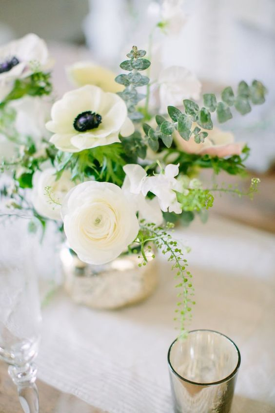a chic wedding centerpiece of white ranunculus and anemones, greenery and eucalyptus plus a mercury glass vase is pure elegance