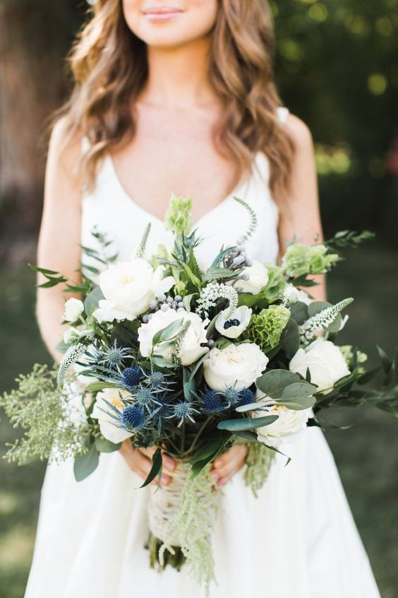a classy wedding bouquet of white peonies, anemones, thistles, greenery with a macrame wrap is a great idea for spring or summer