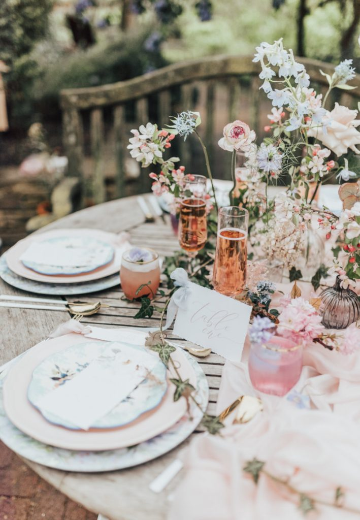 a cluster secret garden wedding centerpiece with various blue and pink blooms and berries is a very fresh idea to rock