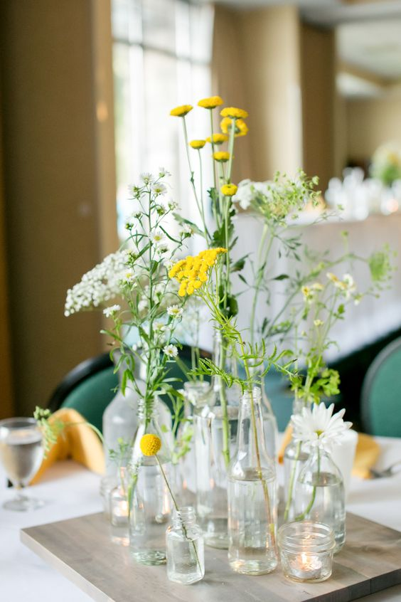 a cluster wedding centerpiece of bottles and vases, daisies and various wildflowers in white and yellow is amazing