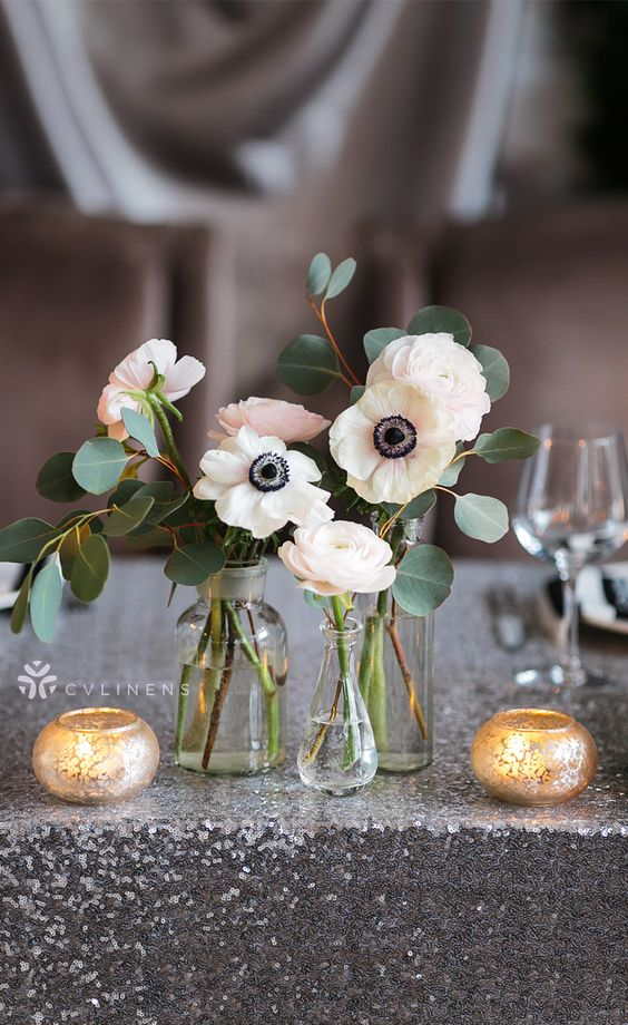 a cluster wedding centerpiece of mismatching vases, white anemones and ranunculus, candles in gilded candleholders