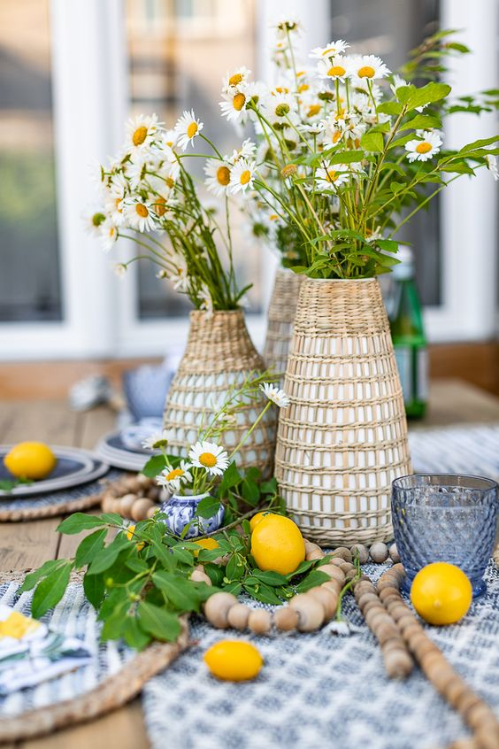 a cluster wedding centerpiece of woven vases with daisies and greenery, wooden beads and lemons on the table