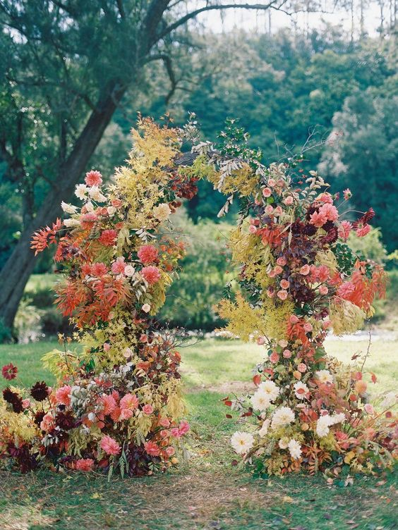 a colorful fall garden wedding arch decorated with greenery and yellow fall leaves, red, burgundy, peachy pink blooms and white flowers