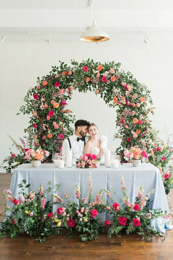 a colorful garden wedding arch covered with greenery and super bold blooms and matching floral arrangements at the table