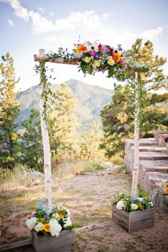 a colorful rustic wedding arch of birch branches and with greenery and super bright blooms is a lovely idea for your rustic wedding