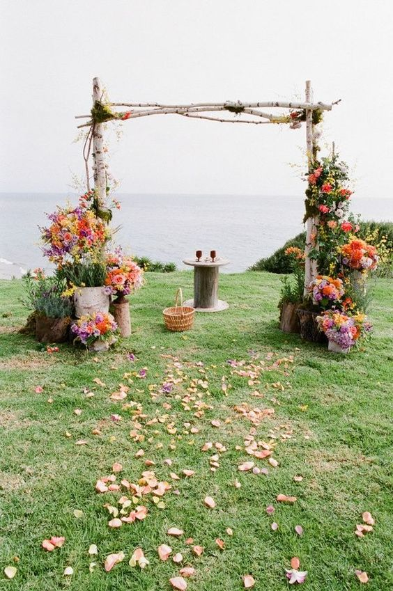 a colorful rustic wedding arch of birch branches, greenery and colorful blooms, petals on the ground and a sea view