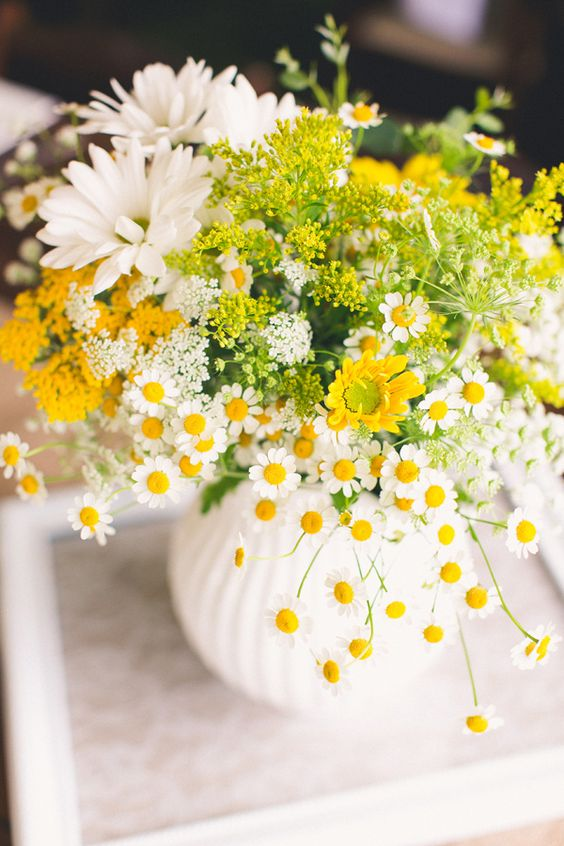 a colorful wedding centerpiece that includes daisies, some yellow and white blooms is a super cool and relaxed wedding decoration idea