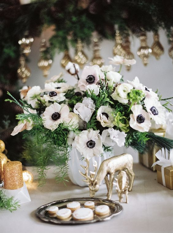 a cool and simple white anemone and evergreen wedding centerpiece in a white vase will match many wedding decor themes