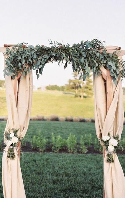 a cool rustic wedding arch covered with neutral burlapm eucalyptus, white floral arrangements attached is a chic decoration