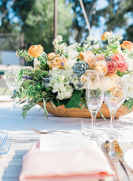a cool secret garden wedding centerpiece of pink, marigold, white blooms, thistles, succulents and greenery is chic