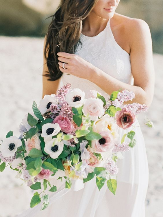 a cool spring wedding bouquet of white anemones, pink peonies and ranunculus, greenery and lilac is amazing