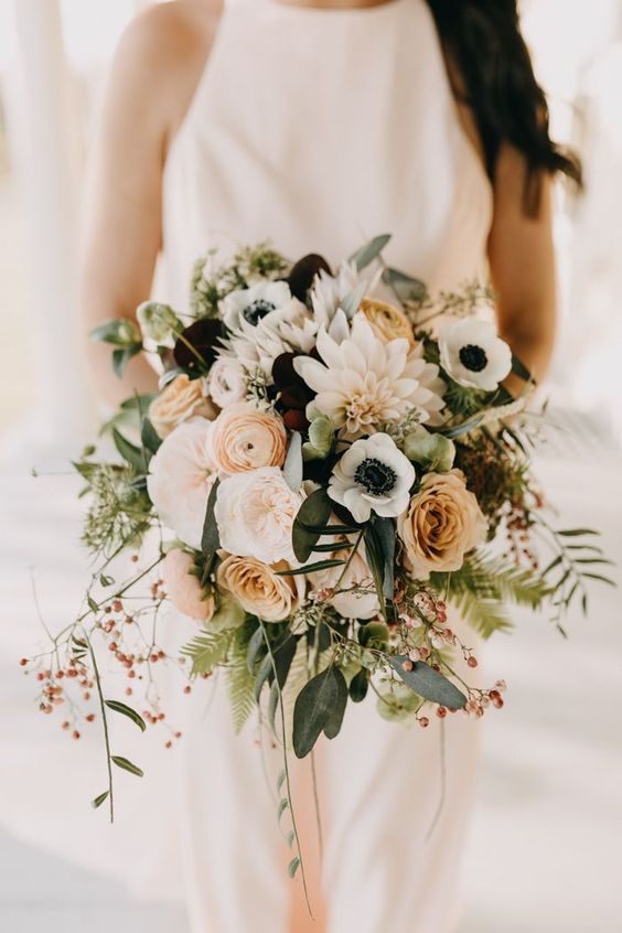 a cool wedding bouquet of rust roses and ranunculus, dark blooms, white anemones and dahlias, greenery and berries