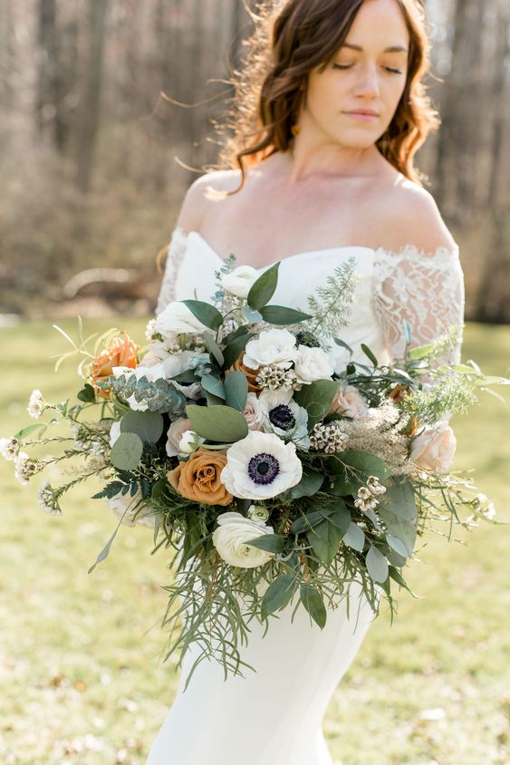 a cool wedding bouquet of white anemones and ranunculus, rust and blush roses, greenery of various kinds is chic and cool