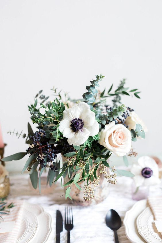 a cool wedding centerpiece of blush roses, white anemones, greenery, privet berries and a cool vase is ideal for spring or summer