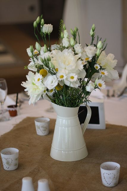 a country style wedding centerpiece of a jug with daises, garden roses in white and some greenery is easy to DIY