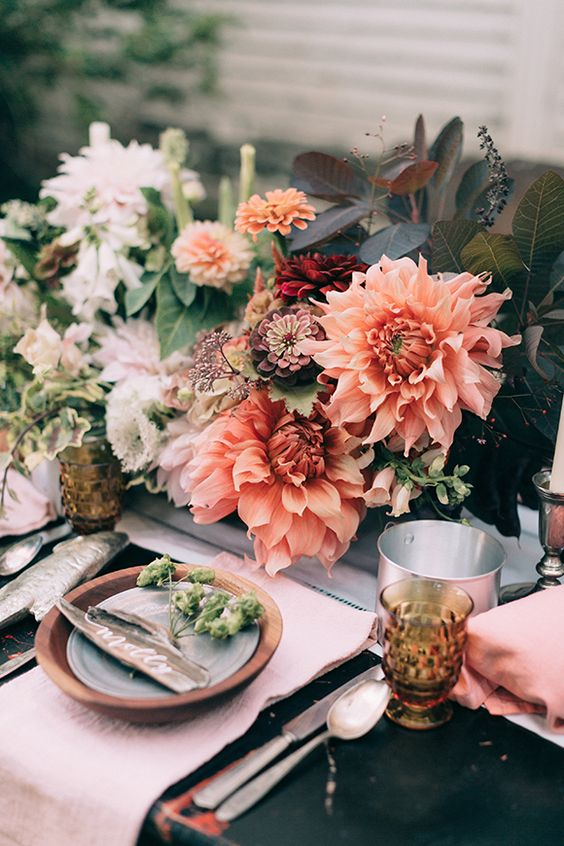 a creative and bright fall wedding centerpiece of dahlias and foliage is a bold and cool idea for your secret garden wedding