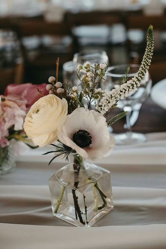 a creative and small wedding centerpiece of a bottle, a white ranunculus and anemone, berries and astilbe is a chic idea for spring or summer