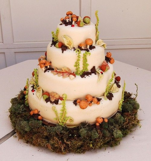 a creative enchanted forest wedding cake in white, with sugar foliage, mushrooms and nuts placed on a moss pillow
