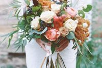 a creative long stem wedding bouquet with white and pink roses, privet berries and cherries, greenery and grasses for a summer bride