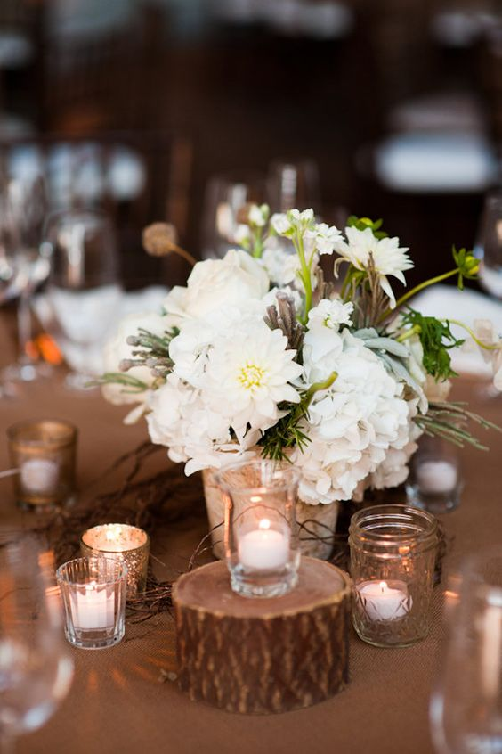 a cute and simple wedding centerpiece of white daisies, hydrangeas and greenery surrounded with candles is ideal for a rustic wedding