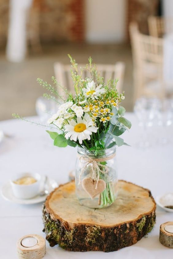 a cute rustic wedding centerpiece of a wood slice, a jar with daisies and some wildflowers plus eucalyptus and a wooden heart