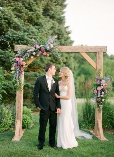 a cute summer rustic wedding arch of wood, greenery, mauve and pink blooms is a cool idea for a rustic summer wedding