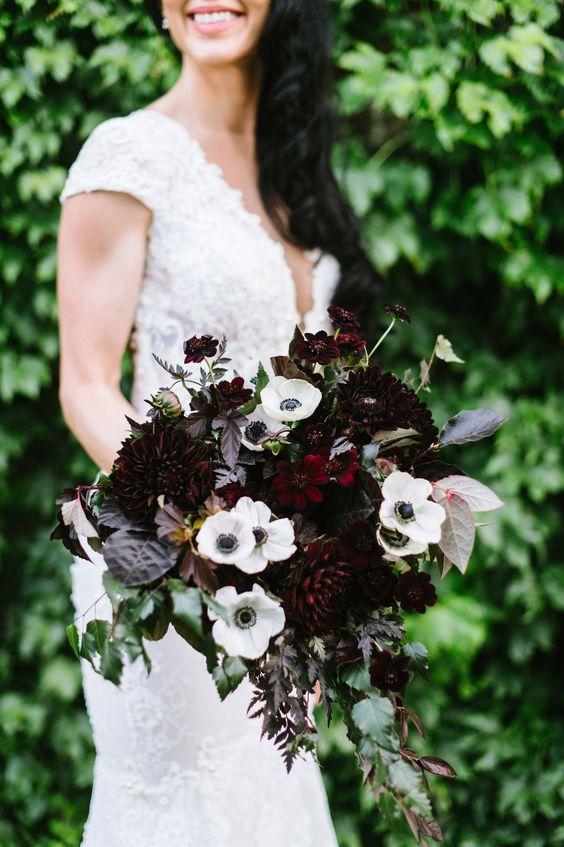a dark winter wedding bouquet of dark dahlias, white anemones, dark foliage and greenery is a lovely idea for a winter wedding