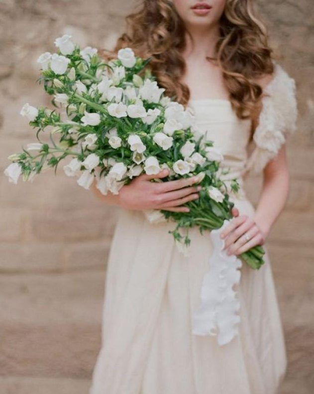 a delicate and feminine bridal look with white foxglove pokes forming a lovely long stem wedding bouquet brings wows