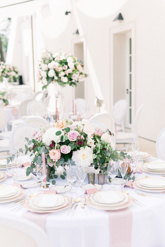 a delicate and refined floral wedding centerpiece with pink, white and burgundy blooms and greenery is ideal for a garden wedding