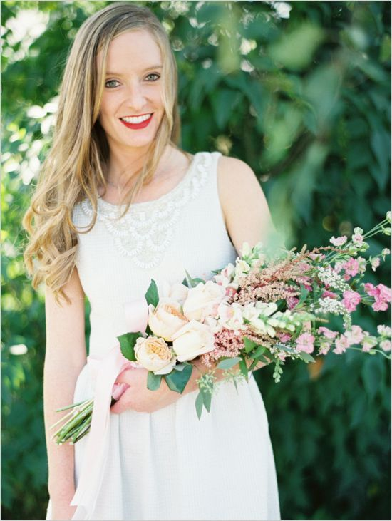 a delicate wedding bouquet of blush peonies, small pink blooms and greenery and blush ribbons for a lovely summer wedding
