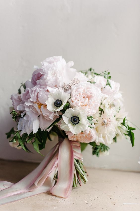 a delicate wedding bouquet of pink peonies and white anemones, pink ribbons and some greenery is ideal for spring or summer