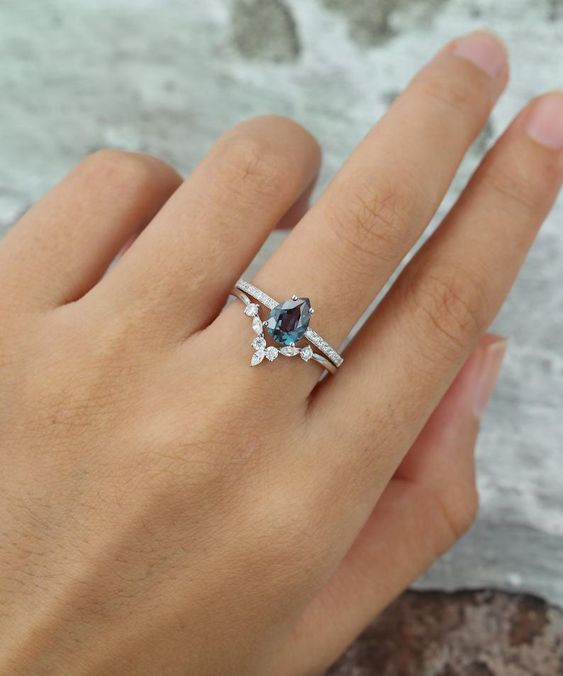 a delicate wedding ring set with a pear-shaped sapphire and a lovely diamond floral lower ring is a very chic idea