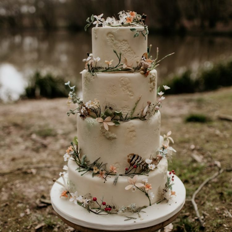 a dreamy enchanted forest wedding cake in white, with sugar patterns, blooms, feathers and berries is a chic idea