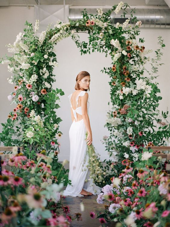 a dreamy garden wedding arch decorated with greenery, white and pink blooms plus arrangements on the floor for a beautiful indoor garden look