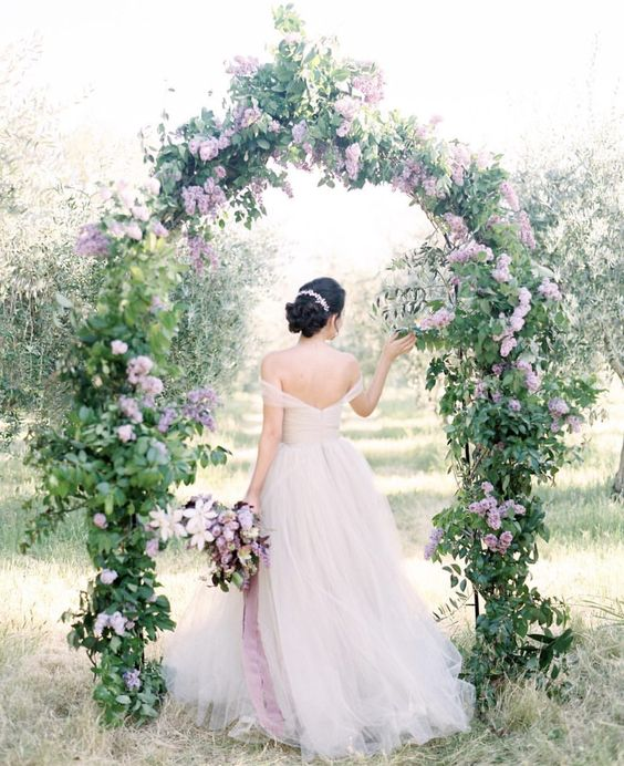a dreamy garden wedding arch with greenery and lilac is a chic idea that looks incredibly romantic and very beautiful