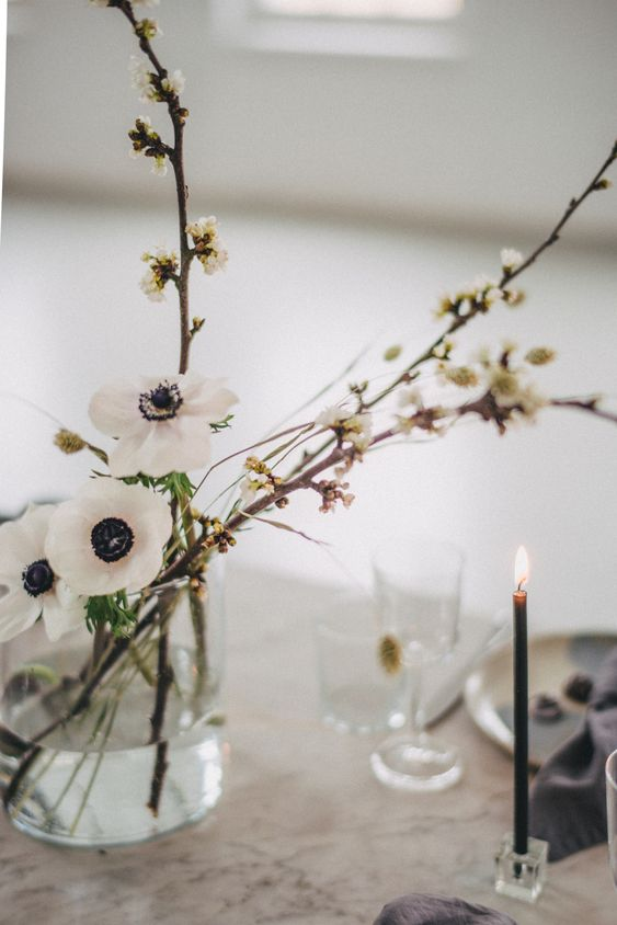 a dreamy minimalist wedding centerpiece of blooming branches and white anemones is a very beautiful idea for a spring wedding