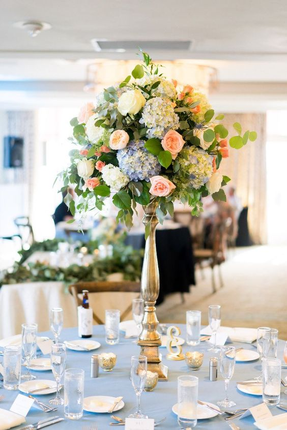 a dreamy tall wedding centerpiece of white, blue and peachy pink blooms and greenery is a lovely and cool idea for a secret garden wedding