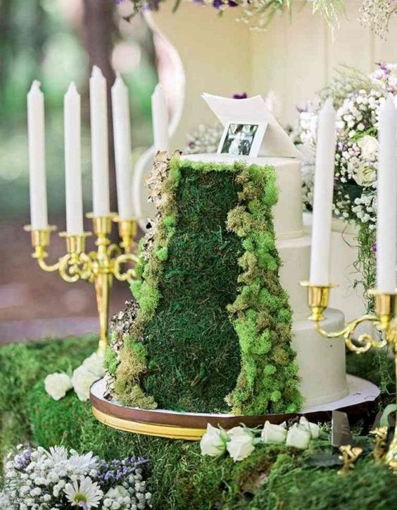 a fabulous enchanted forest wedding cake with moss and grass decor and a photo topper is a unique idea