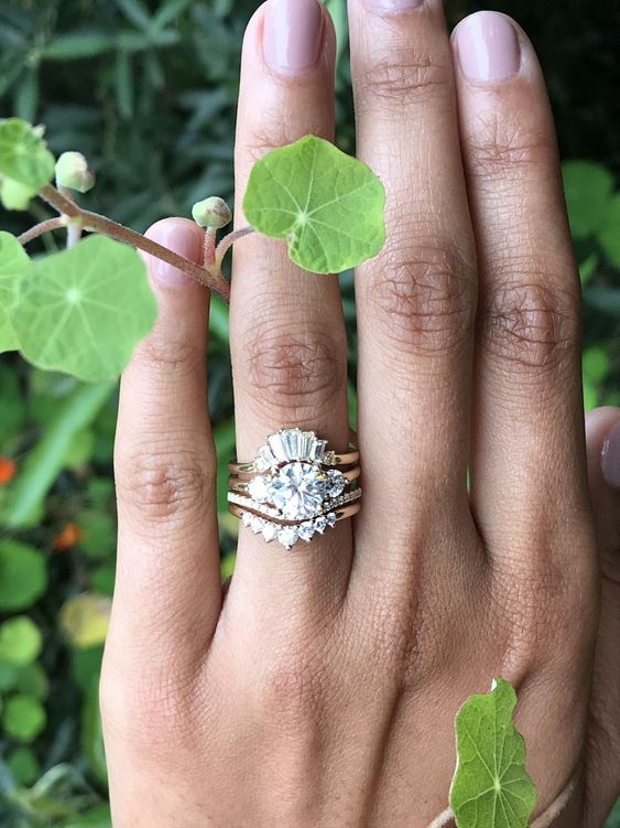 a fabulous stacked engagement ring with a central statement one, two arched lower bands with smaller diamonds and a top small diamond ring