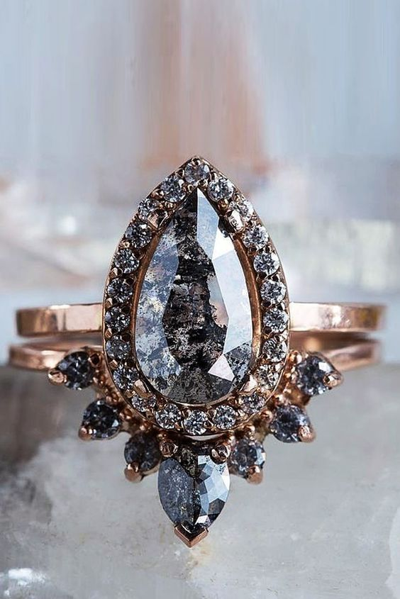 a fantastic rose gold stacked engagement ring with a pear-shaped solitaire with smaller diamonds framing it and a lower arched diamond ring for framing