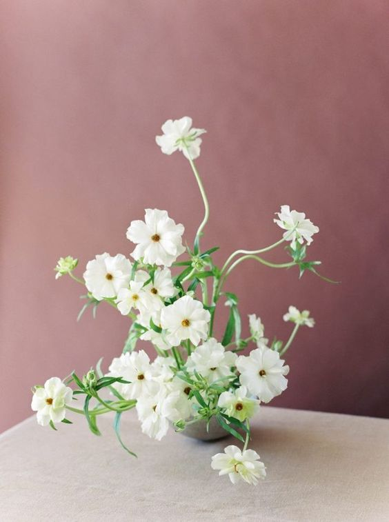 a fine art wedding centerpiece of grey vase and white blooms is a very lovely idea for a spring or summer modern wedding