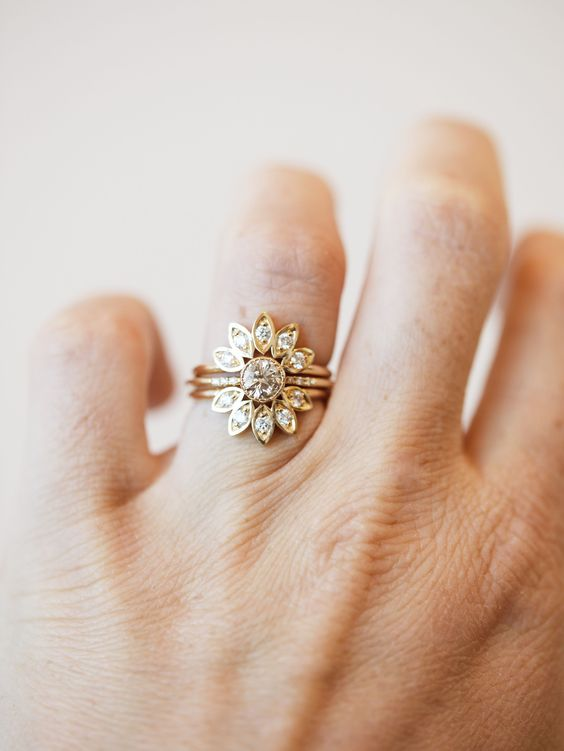 a floral stacked engagement ring with a center round diamond and petal arched upper and lower rings is very cool