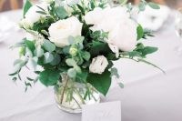 a fresh and stylish wedding centerpiece of various types of greenery, white peonies in a sheer vase is a lovely idea