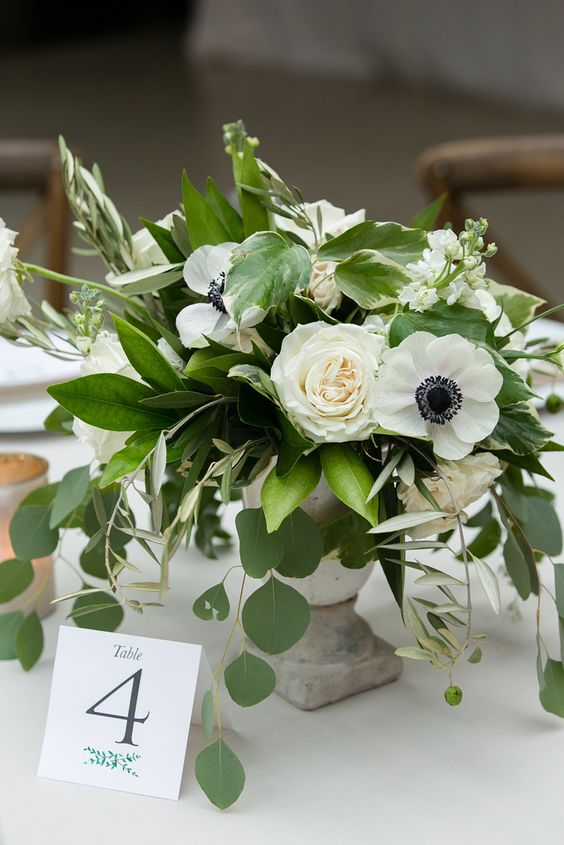 a fresh wedding centerpiece of white peonies and anemones and various types of greenery in a vintage urn is very cool