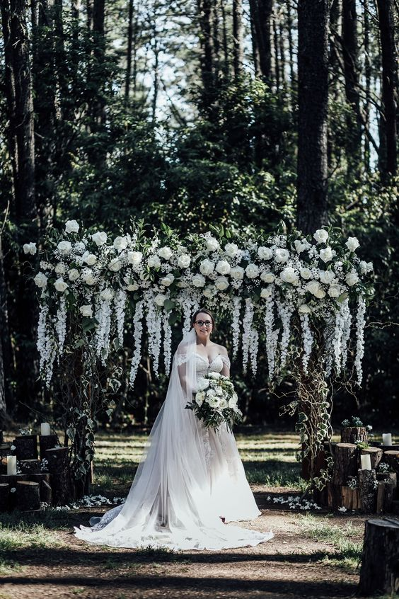 a gorgeous and very lush wedding arch covered with foliage and lots of white blooms on top and hanging down