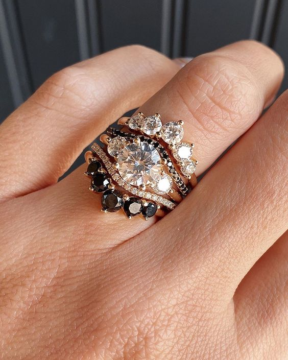 a gorgeous stacked wedding ring with a central band with a large round diamond and two smaller ones, two arched rings with black and white diamonds, arched bands with larger diamonds