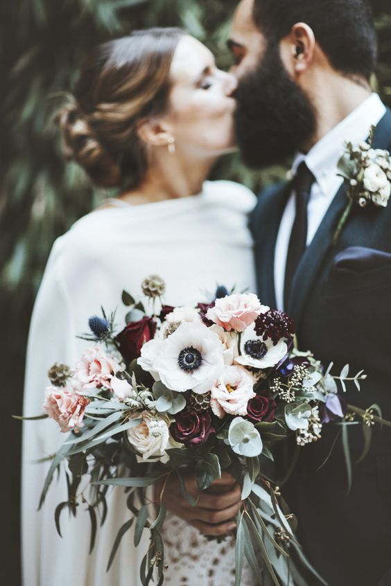 a gorgeous wedding bouquet of white anemones, blush roses, greenery, dark blooms and thistles looks textural and very cool
