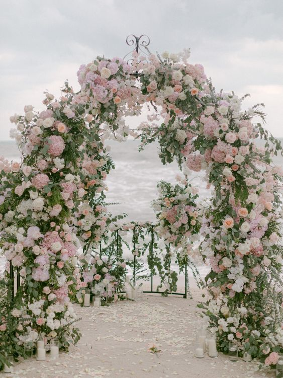a jaw-dropping beach garden wedding arch decorated with greenery, white, blush and mauve blooms is just jaw-dropping and chic